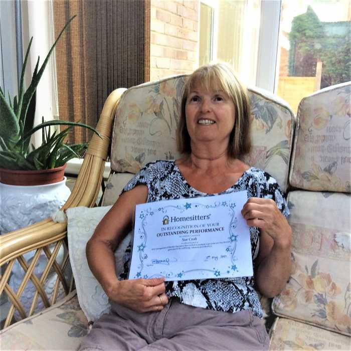 homesitter Sue Croft with her certification in recognition of her outstanding performance